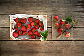 Fresh strawberries in a crate and on a wooden board