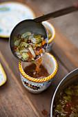 Gemüsesuppe in Schälchen füllen
