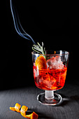 Negroni with a smoldering rosemary sprig