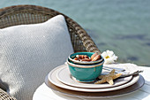 A bowl of chocolates at a place setting with a starfish on a table on the beach