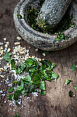 Pesto ingredients in a mortar with a pestle