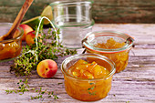 Homemade apricot jam with fresh thyme in a mason jar