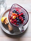 Zutaten für Smoothie (Himbeere, Heidelbeere, Apfel, Zitrone) im Mixer