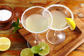 Two glasses of margarita with salted rims, tequila, orange liqueur and lemon