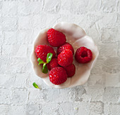 Raspberries in a bowl with a mint leaf