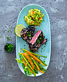 Tuna in a black sesame seed coating with guacamole and an asparagus and pepper meldey