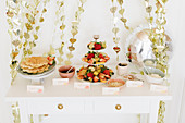 Waffles and fruits on party buffet table and garlands of shiny hearts