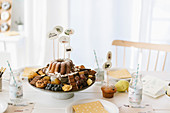 Sweets, fruits and cake on cake stand with decorative skewers