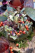 Strauß aus Hagebutten, Hortensie und Eukalyptus in Kürbis als Vase