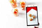 Hand hält Handy mit Foto von geschnittenen Zitrusfrüchten
