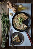 From above of skillet pan with fried tortilla with fresh asparagus and onion served on board with ingredients
