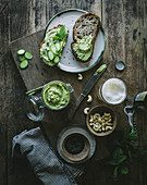 From above toasts with green cashew pate and slices of cucumber on wooden board