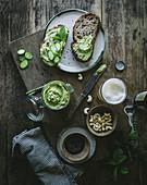 Toast mit grüner Cashewpaste und Gurkenscheiben auf Holzbrett
