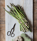 Top view of marble board with pile of asparagus tied with twine rope on wooden table