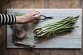 Top view of person hands holding scissors in marble board with pile of asparagus tied with twine rope on wooden table