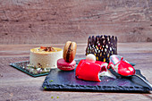 Arrangement of raspberry vanilla dessert on slate board with macaroons served on wooden table