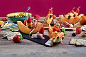 Melone mit Schinken, Oliven und Erdbeeren für eine Party