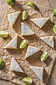 Key lime bars triangles with lime slices on butcher paper