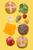 Different ingredients of a cheese burger wrapped in plastic on yellow background