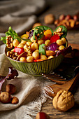 From above appetizing colorful cut vegetable mix with chickpeas and walnuts on wooden background