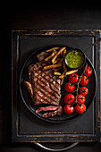 Sirloin steak with griled tomatoes, french fries and salsa verde sauce