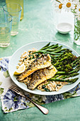 Pan fried sea bass fillets with creamy orzo and spinach pasta and fresh greens