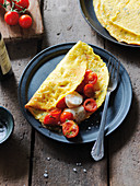 Stuffed sweetcorn crepes with tomatoes