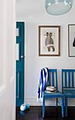 Blau-weiß gestreifter Schal über blauen Stühlen im Flur