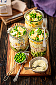Layer salad in jar - broccoli, pasta, ham, egg, sauce, corn, pineapple and green peas
