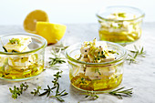 Pickled feta cheese in olive oil with garlic, spring onions, thyme, rosemary and lemon pepper