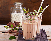 Chilled chocolate-mint milk in glasses with straws