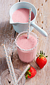 A creamy strawberry and coconut shake with a straw