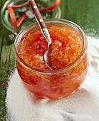 A jar of citrus fruit marmalade on a pile of jam sugar