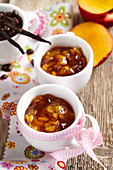 Coffee and vanilla flavoured nectarine jam in cups with a bow