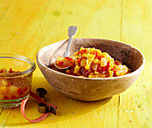 Melon chutney with star fruit, pepper, allspice and vinegar in a wooden bowl