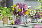 Sträuße aus Flieder, Wolfsmilch, Akelei und Tränendem Herz in alten Teekesseln, Topf mit Salat und Koriander