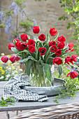 Strauß aus roten Tulpen in Glasvase