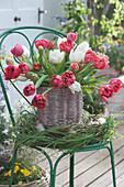 Tulpenstrauß in Korbvase in Kranz aus Gräsern und Zweigen