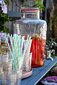 Glasses, straws and punch in glass dispenser on garden table