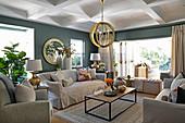 Helle Polstermöbel, Couchtisch und gold lackierte Hängelampe im Wohnzimmer mit graugrünen Wänden