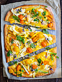 Pizza with yellow zucchini, tomatoes and ricotta
