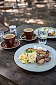 A sumer breakfast al fresco with scrambled eggs, bacon and cappuccinos