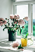 An orange juice and wine cocktail next to a bunch of peonies on a window sill