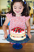Little girl with a berry cake