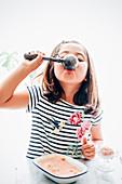 Mädchen isst Pfirsichsorbet aus Eiskugelformer