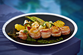 Scallops wrapped in bacon with vegetables