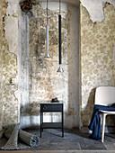 Aufgerollter Teppich, Beistelltisch, Pendelleuchten und Stuhl im Zimmer mit abgeblätterter Tapete
