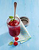 A jar of mango and raspberry jam with fresh lemon balm