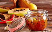 Papaya and orange chutney with curry and hot peppers in a jar
