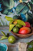 Mango und Limetten in Holzschüssel
